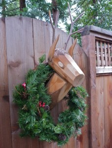 A wooden reindeer on fence on Olive St. sports a holiday wreath.