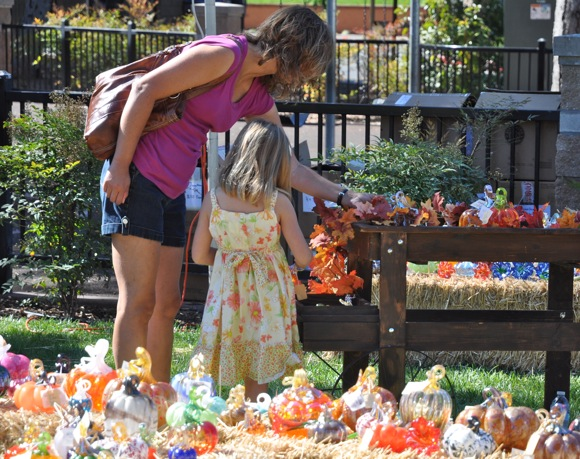 Mother and daughter inspect the glass pumpkins for sale at Nativity School