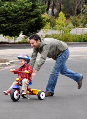 toddler hurries to get his bik