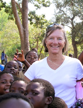 visitor to Malawi surrounded by villagers