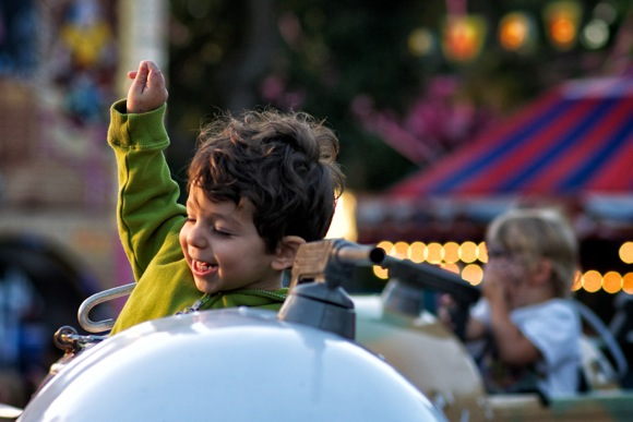 Young child enjoying rocket ride at 2012 Nativity Carnival