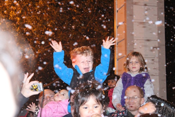 Child greets the snow and holiday train in Menlo Park