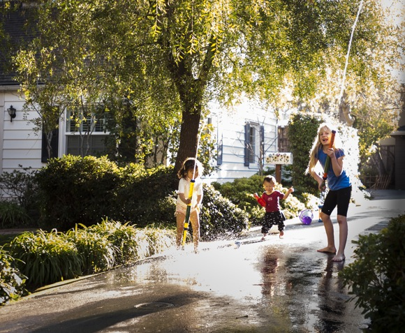 children play in sprinklers in January in Menlo Park