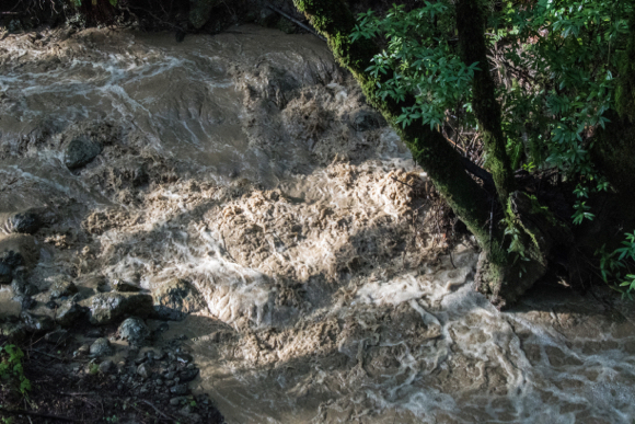 Rain turns Damiani Creek into a rolling, boiling torrent
