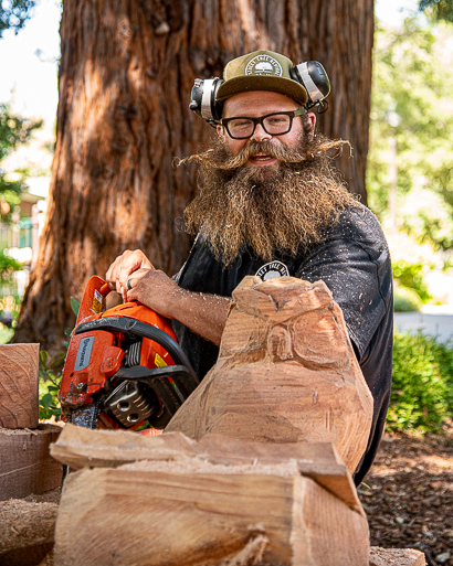 Big John Mahoney turns redwood logs into story time benches at Menlo Park Library